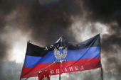 Smoke from a buring proRussian activist blockade rises around a flag of the Donetsk Republic following an assault by the Ukrainian army on May 3 2014...