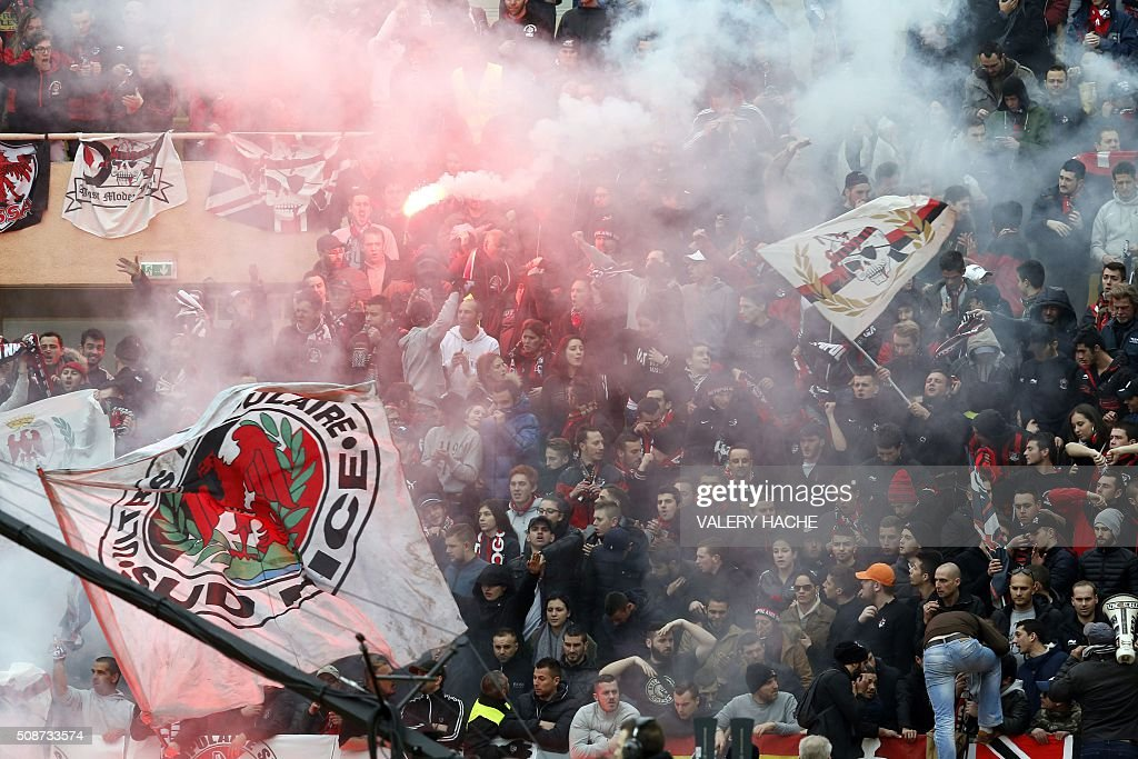 Smoke from a burning flare rises over Nice supporters cheering during the French L1 football match between Monaco (ASM) and Nice (OGCN) at Louis II Stadium in Monaco on February 6, 2016. AFP PHOTO / VALERY HACHE / AFP / VALERY HACHE