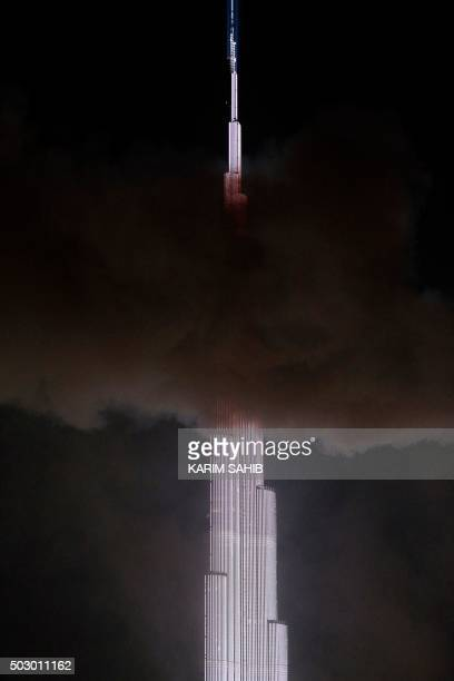 Smoke from a fire that ripped through the Address Downtown hotel billows past the Burj Khalifa the world's tallest tower in Dubai on December 31 2015...
