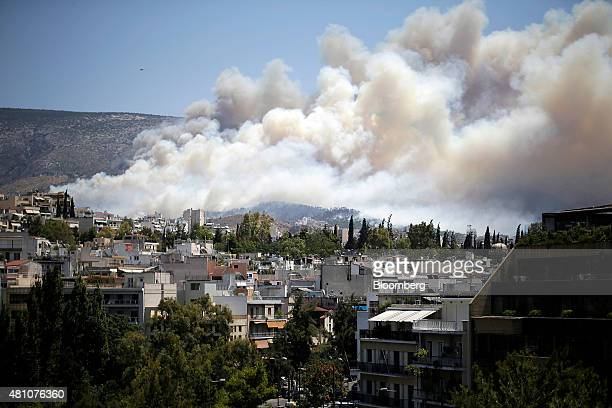 Smoke from a forest fire covers the hillsides near the eastern residential suburbs of Athens Greece on Friday July 17 2015 Germany's Parliament is...