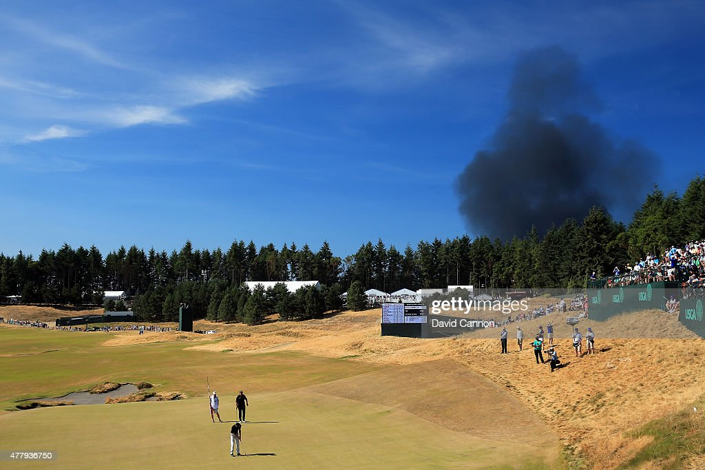 Smoke from a local fire is seen above the 13th green during the third round of the 115th US Open Championship at Chambers Bay on June 20 2015 in...