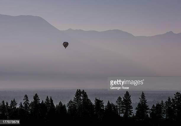 Smoke from a nearby forest fire drifts over Lake Tahoe nearly obscuring a hot air balloon on August 4 in South Lake Tahoe California Lake Tahoe...
