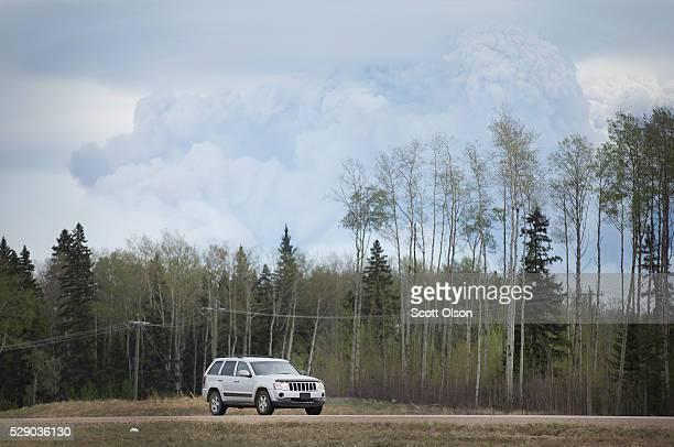 Smoke from a wildfire rises above Hiway 63 on May 7 2016 near Fort McMurray Alberta Wildfires which are still burning out of control have forced the...