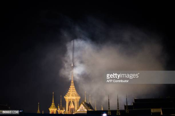Smoke from artillery gun salvos being fired nearby envelops part of the main pavilion in the cremation grounds where the body of late Thai King...