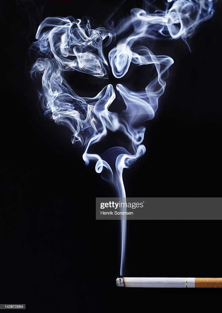 smoke from cigarette formed like cranium : Stock Photo