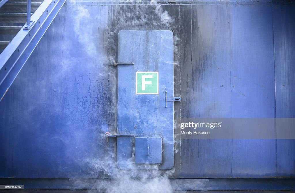 Smoke from fire behind steel door in fire simulation training facility