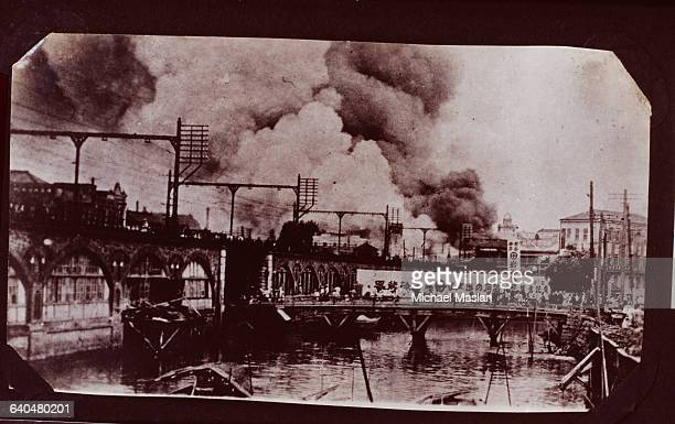 Smoke from fires caused by the 1923 Yokohama earthquake rises beyond a bridge where people stand watching