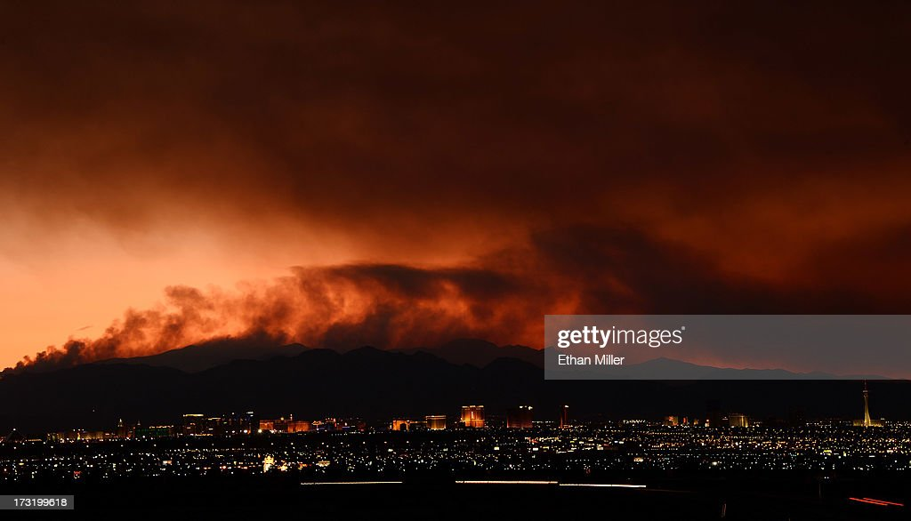 Smoke from the Carpenter 1 fire in the Spring Mountains range is illuminated by the setting sun as it billows behind hotel-casinos on the Las Vegas Strip on July 9 2013 in Las Vegas, Nevada. Nearly 20,000 acres have burned since lightning sparked the blaze in Carpenter Canyon on the Pahrump, Nevada side of Mount Charleston on July 1. More than 800 firefighters are battling the wildfire which crested the peak of Mount Charleston on Thursday, prompting the evacuation of 520 people as it began descending the east side of the mountain, about 35 miles northwest of Las Vegas. The fire is 15% contained and fire officials estimate that they won't have it fully contained until July 19.