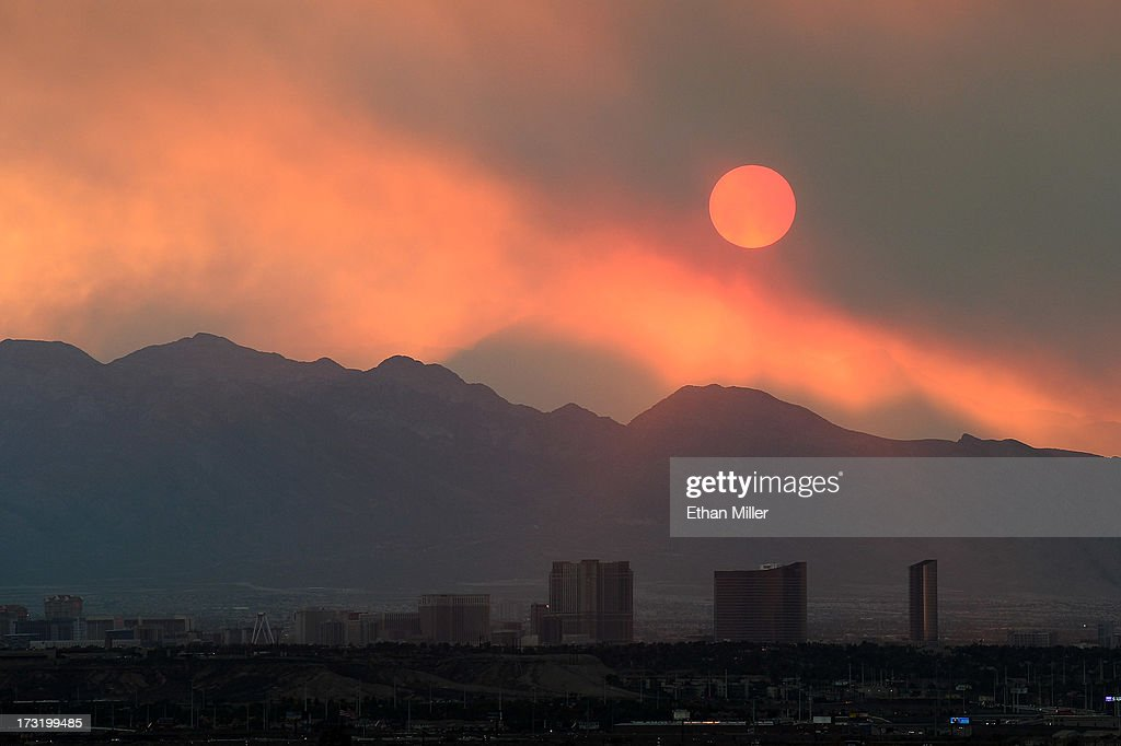 Smoke from the Carpenter 1 fire in the Spring Mountains range partially obscures the setting sun behind hotel-casinos on the Las Vegas Strip on July 9 2013 in Las Vegas, Nevada. Nearly 20,000 acres have burned since lightning sparked the blaze in Carpenter Canyon on the Pahrump, Nevada side of Mount Charleston on July 1. More than 800 firefighters are battling the wildfire which crested the peak of Mount Charleston on Thursday, prompting the evacuation of 520 people as it began descending the east side of the mountain, about 35 miles northwest of Las Vegas. The fire is 15% contained and fire officials estimate that they won't have it fully contained until July 19.