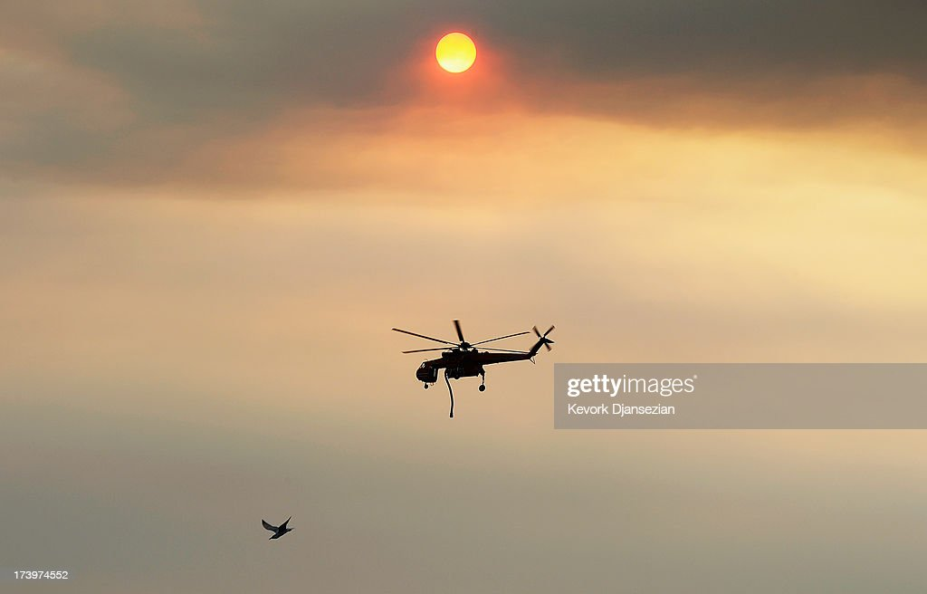 Smoke from the Mountain Fire obscures the sun as a fire-fighting helicopter drops down to pick water from Lake Hemet to fight the out to control Mountain Fire with a Seagull bird flying bye on July 18, 2013 in Idyllwild, California. The massive wildfire in Riverside County has grown to 23,000 acres and is advancing towards the mountain town of Idyllwild on one front and city of Palm Springs on the other front destroying several homes and forcing the evacuation of 6,000 people.