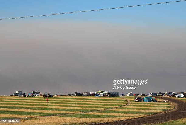 Smoke from wildfires darkens the sky as earlier visitors set up camp at 'SolarTown' in Madras Oregon August 17 2017 ahead of the total solar eclipse...