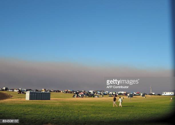 Smoke from wildfires darkens the sky as visitors set up camp at 'SolarTown' in Madras Oregon on August 17 to see the total solar eclipse on August 21...