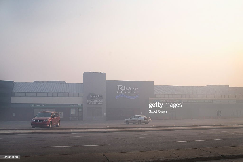 Smoke from wildfires fill the morning air in front of a shopping center on May 6, 2016 in Fort McMurray, Alberta, Canada. Wildfires, which are still burning out of control, have forced the evacuation of more than 80,000 residents from the town.