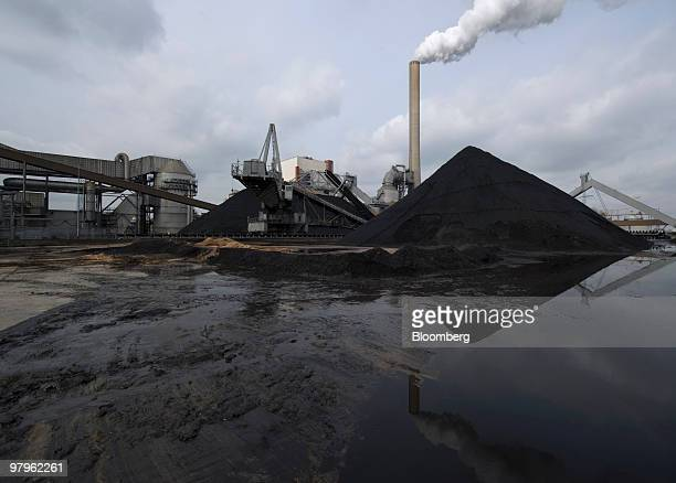 Smoke is emitted from a chimney behind a stack of coal at a RWE AG owned Essent Energie power station in Geertruidenberg Netherlands on Monday March...