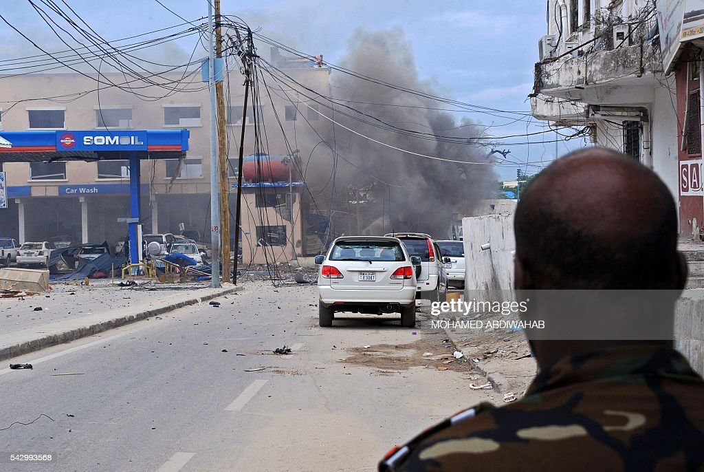 Smoke is seen at the scene of a car bomb attack claimed by Al-Qaeda-affiliated Shabaab militants which killed at least 5 people, on the Naasa Hablood hotel in Mogadishu on June 25, 2016. The hotel in southern Mogadishu is often used by politicians and members of the Somali diaspora visiting the city. The attack came just three weeks after another assault quickly claimed by the Al-Qaeda-linked Shabaab group on the city's Ambassador hotel left 10 dead including two lawmakers when a huge car bomb ripped the front off the six-storey building. / AFP / MOHAMED