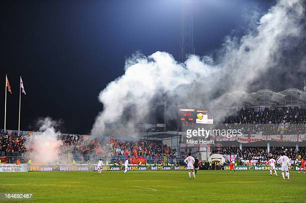 Smoke moves across the pitch as a flare is ignited during the FIFA 2014 World Cup Qualifier Group H match between Montenegro and England at City...