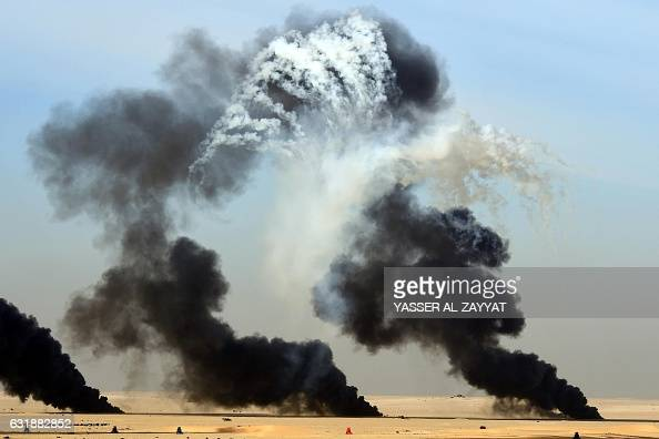 TOPSHOT Smoke plumes rise during a live ammunition military exercise at Udaira military range 140 km north of Kuwait City on January 17 2017 / AFP /...
