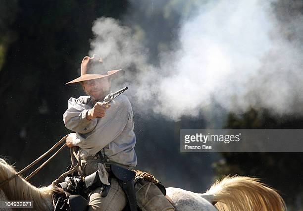 Smoke pours from the revolver of a Confederate soldier riding horseback during a battle reenactment at the 21st annual Civil War Revisited event at...