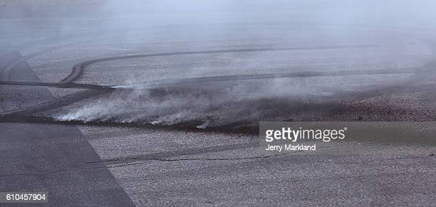 Smoke radiates from the track after Kevin Harvick's burnout celebration after winning the NASCAR Sprint Cup Series Bad Boy Off Road 300 at New...