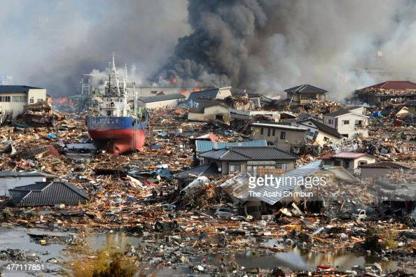 Smoke rise from debris while a trawler stranded after washed onto land by tsunami at the Kensennuma city center after a 90 magnitude strong...