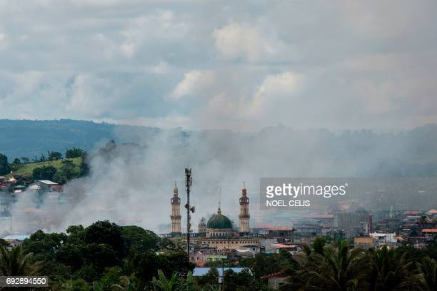 TOPSHOT Smoke rises after aerial bombings by Philippine Air Force planes on Islamist militant positions in Marawi on the southern island of Mindanao...