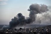 Smoke rises after an airstrike from USled coalition in the city of Kobane also known as Ain alArab seen from the southeastern border village of...