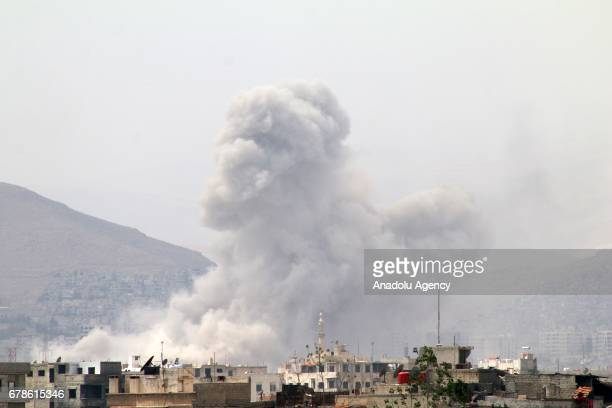 Smoke rises after Assad regime forces attacked opposition controlled Qaboun district of Damascus Syria on May 04 2017 Regime forces hit residential...