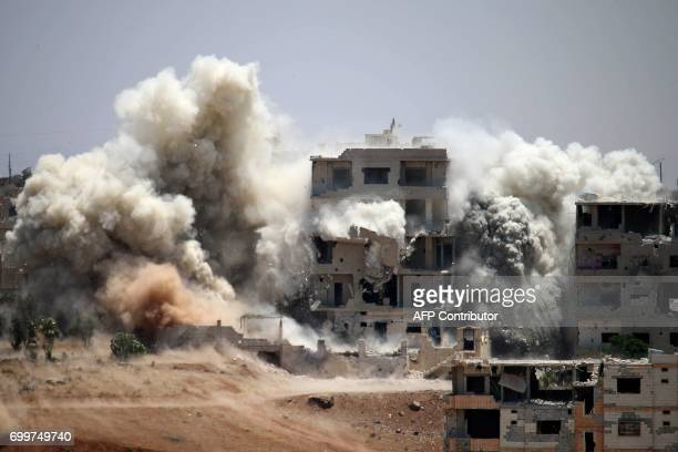 TOPSHOT Smoke rises around buildings following a reported air strike on a rebelheld area in the southern Syrian city of Daraa on June 22 2017 / AFP...