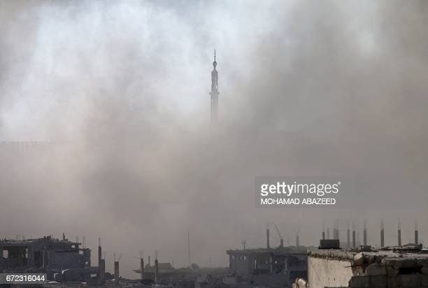 TOPSHOT Smoke rises around the minaret of a mosque following a reported air strike on a rebelheld area of the southern Syrian city of Daraa on April...