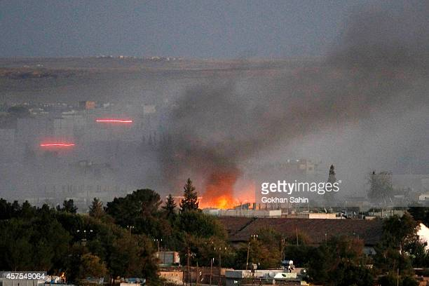 Smoke rises as bullets with tracers fly through the air after an explosion rocks Syrian city of Kobane during a reported suicide car bomb attack by...