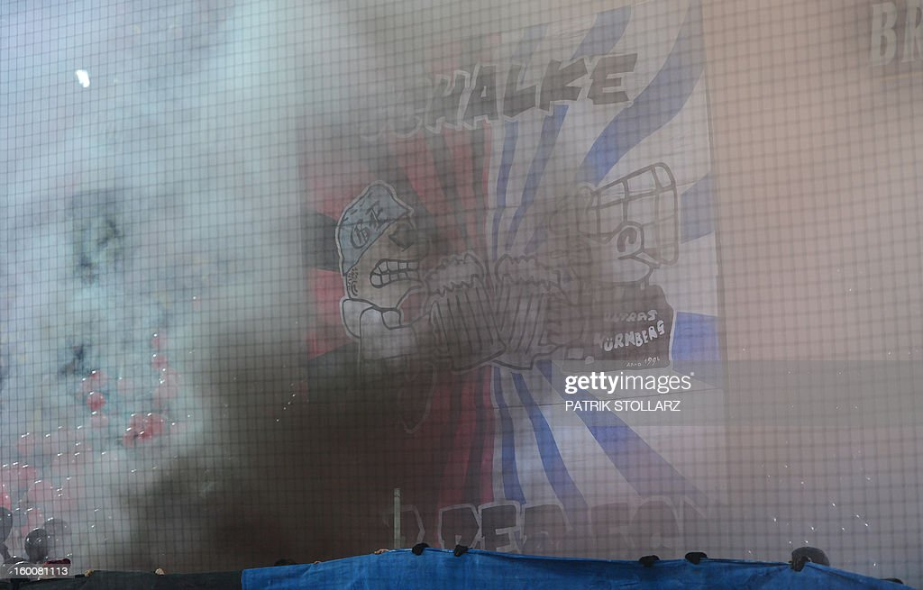 Smoke rises as Nuremberg´s supporters throw granates during the German first division Bundesliga football match Borussia Dortmund vs FC Nuremberg in Dortmund, western Germany on January 25, 2013.