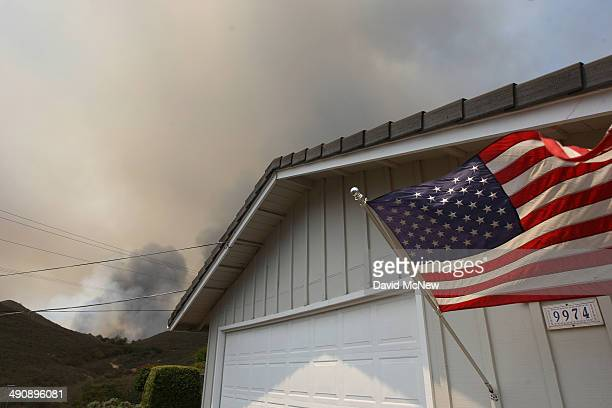 Smoke rises as the southeast flank of the Cocos fire bears down on houses near Del Dios Highway on May 15 2014 near San Marcos California Fire...