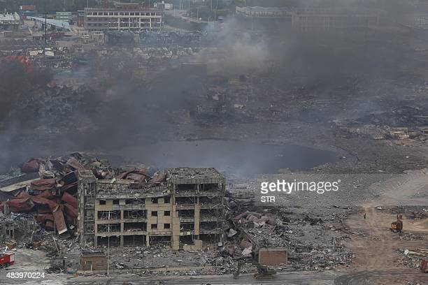 Smoke rises at the site of an explosion in Tianjin on August 14 2015 Chinese authorities struggled to extinguish fires and identify dangerous...
