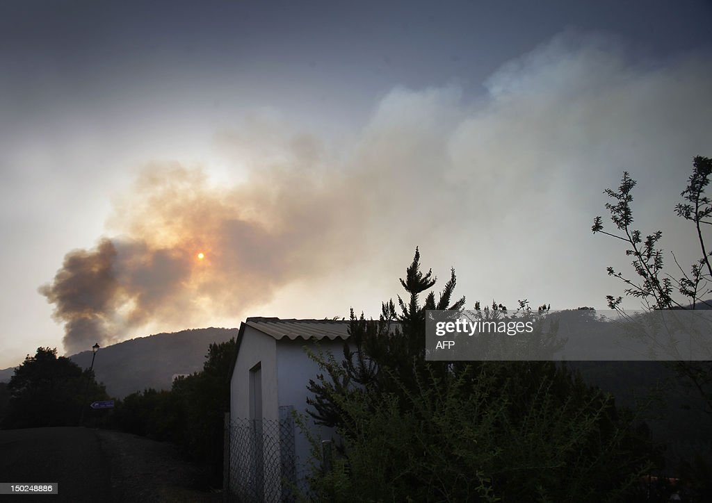 Smoke rises behind the village of Las Hayas on August 13, 2012, on the Spanish canary island of La Gomera. Wildfires killed two people in south-eastern-Spain and forced thousands to evacuate in the Canary Islands where flames ravaged a rare nature reserve, authorities said Monday.