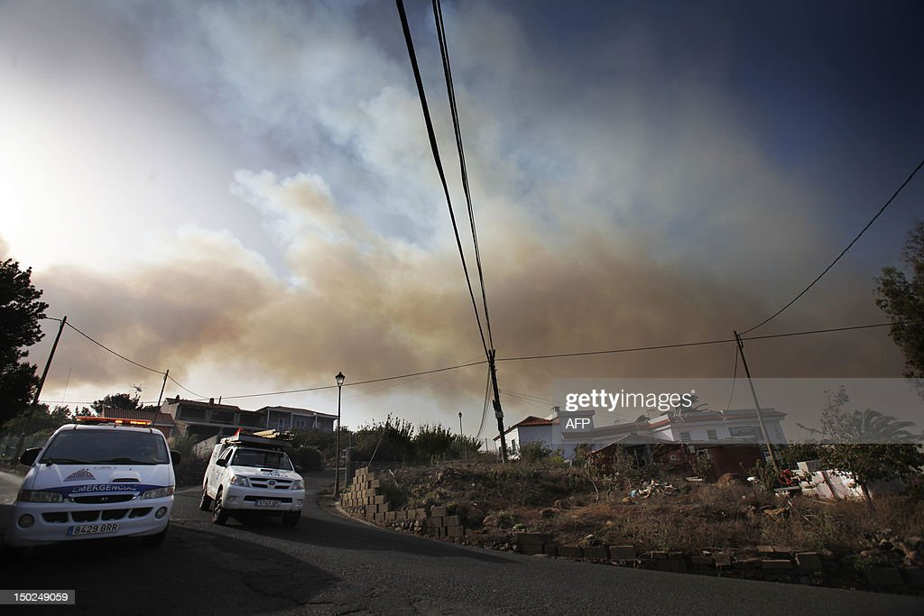 Smoke rises behind the village of Las Hayas on August 13, 2012, on the Spanish canary island of La Gomera. Wildfires killed two people in south-eastern-Spain and forced thousands to evacuate in the Canary Islands where flames ravaged a rare nature reserve, authorities said today. AFP PHOTP / DESIREE MARTIN