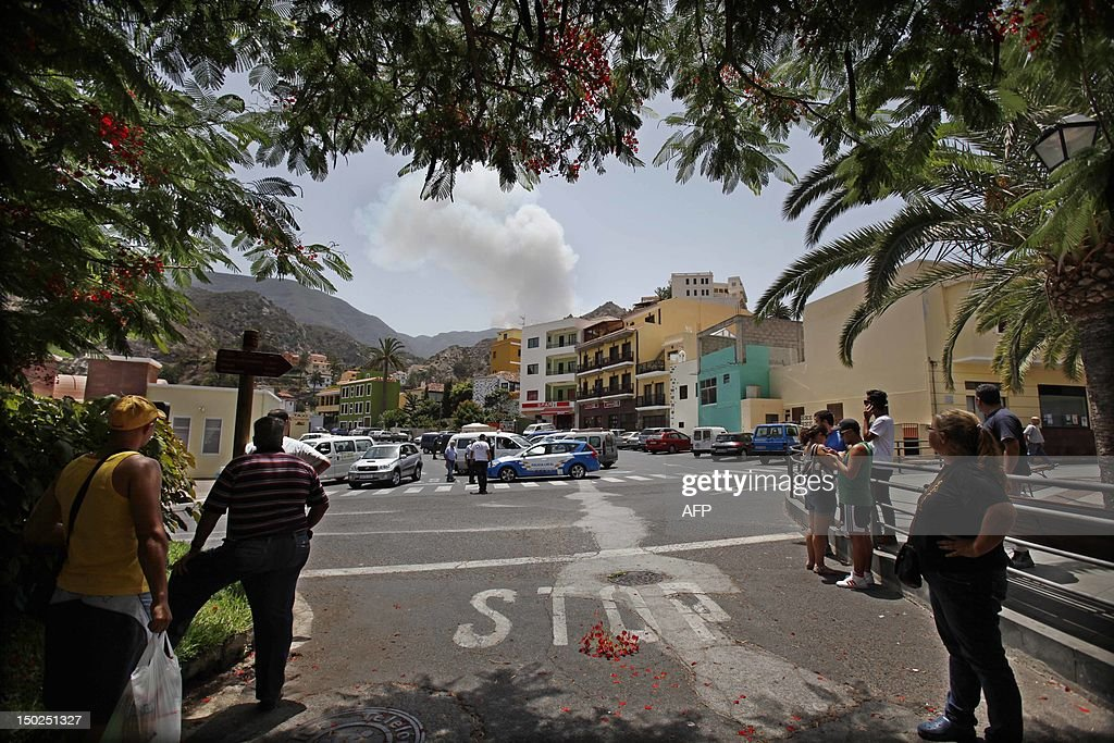Smoke rises behind the village of Vallehermoso on August 13, 2012, on the Spanish canary island of La Gomera. Wildfires killed two people in south-eastern-Spain and forced thousands to evacuate in the Canary Islands where flames ravaged a rare nature reserve, authorities said Monday. AFP PHOTP / DESIREE MARTIN