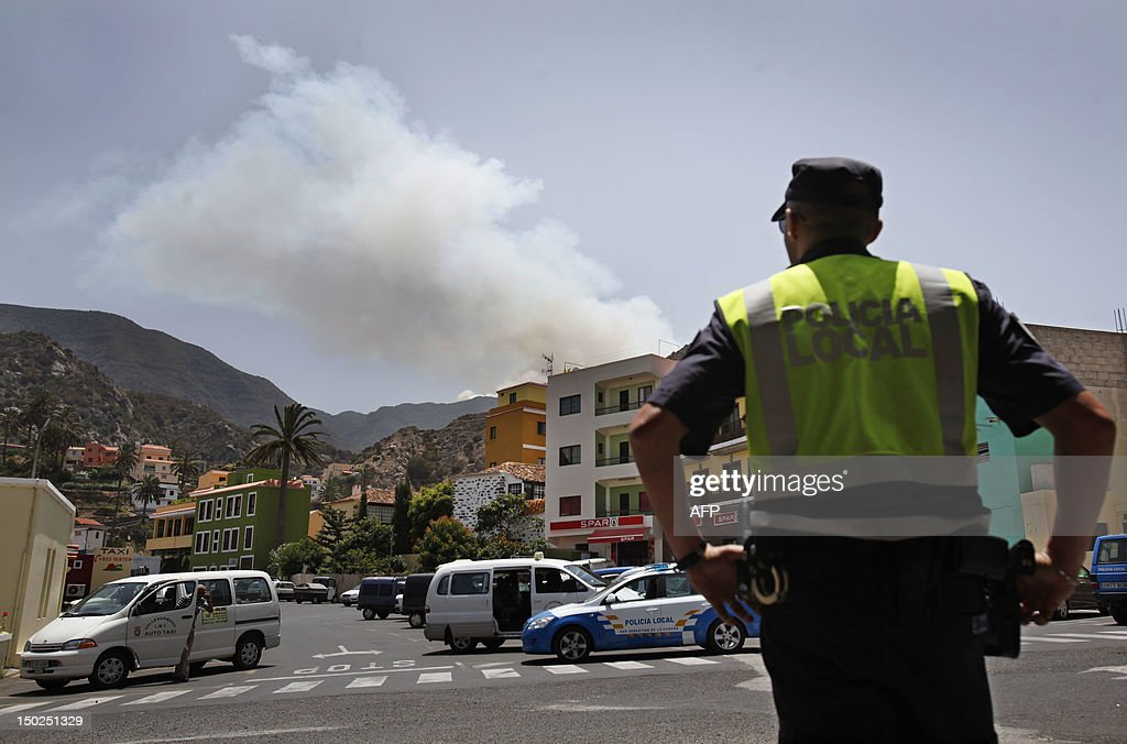 Smoke rises behind the village of Vallehermoso on August 13, 2012, on the Spanish canary island of La Gomera. Wildfires killed two people in south-eastern-Spain and forced thousands to evacuate in the Canary Islands where flames ravaged a rare nature reserve, authorities said Monday.