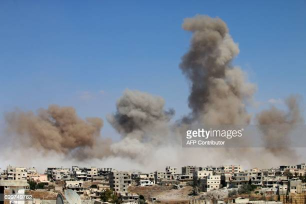 TOPSHOT Smoke rises following a reported air strike on a rebelheld area in the southern Syrian city of Daraa on June 22 2017 / AFP PHOTO / Mohamad...