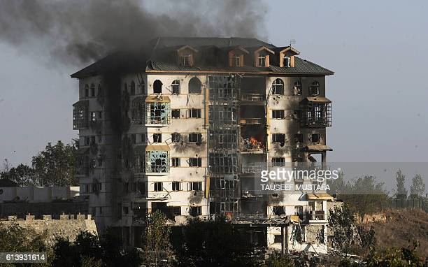 Smoke rises from a building where suspested militants are thought to be hiding on the second day of a gunfight between the army and suspected...