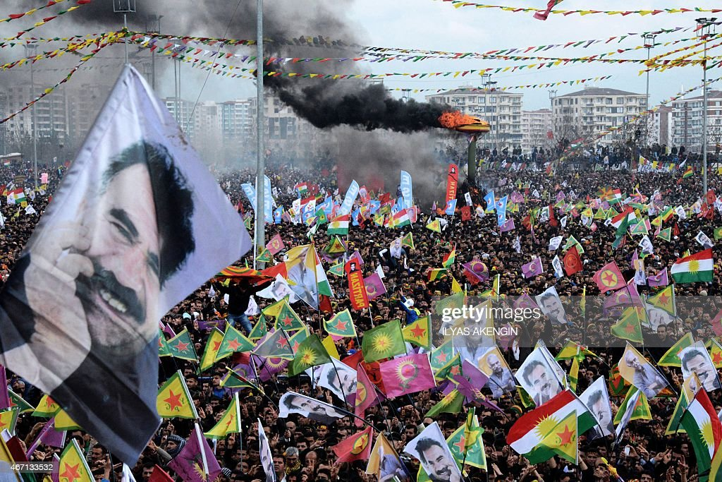 Smoke rises from a fire burning as people wave Kurdish flags and pictures of jailed Kurdish rebel leader <a gi-track='captionPersonalityLinkClicked' href=/galleries/search?phrase=Abdullah+Ocalan&family=editorial&specificpeople=658599 ng-click='$event.stopPropagation()'>Abdullah Ocalan</a> as they gather to celebrate Newroz, the Kurdish New Year, in the southeastern Turkish city of Diyarbakir, on March 21, 2015. Newroz, which means 'new day' in Kurdish and marks the first day of Spring, is also celebrated in Iran, Afghanistan, Azerbaijan, Albania, Bahrain, Georgia, Turkmenistan, Tajikistan, Uzbekistan, Kyrgyzstan and Kazakhstan, as well as among various other Iranian and Turkic peoples in Iraqi Kurdistan, Syria, Lebanon, Pakistan, India, northwestern China, the Caucasus, the Crimea, and the Balkans. AFP PHOTO / ILYAS AKENGIN