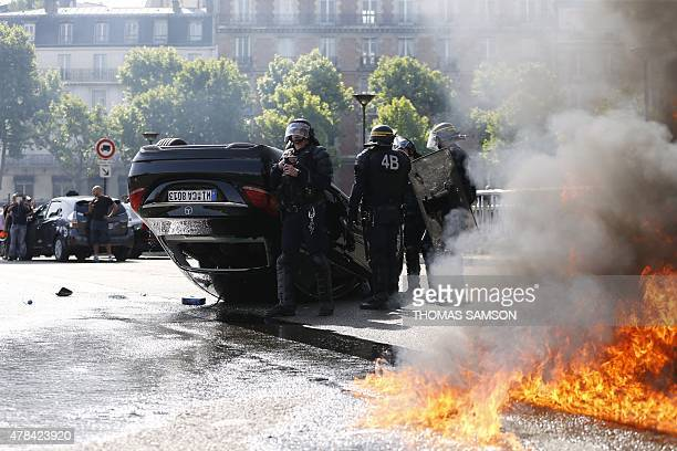 Smoke rises from a fire burning next to French CRS riot police standing near an overturned car as taxi drivers block Porte Maillot in Paris on June...