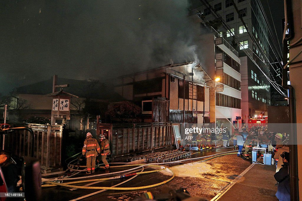 Smoke rises from an old establishment soba (Japanese noodle) restaurant 'Kanda Yabusoba' in Tokyo on February 19, 2013. No one was injured but the 1880 established wooden made restauramt was burnt down.