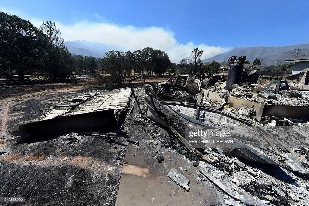 Smoke rises from behind the mountains amid the remains from a demolished home in the community of Squirrel Valley in Lake Isabella, California on June 24, 2016. An intense wildfire broke out yesterday afternoon scorched dozens of homes and structures in this mountainous community northeast of Bakersfield in Kern County. / AFP / FREDERIC