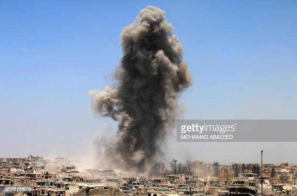 Smoke rises from buildings following a reported air strike on a rebelheld area in the southern Syrian city of Daraa on May 22 2017 / AFP PHOTO /...