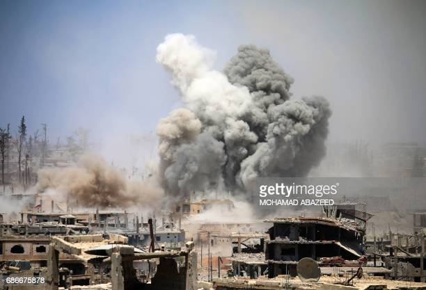 TOPSHOT Smoke rises from buildings following a reported air strike on a rebelheld area in the southern Syrian city of Daraa on May 22 2017 / AFP...