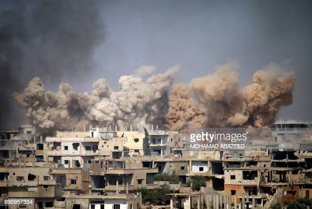TOPSHOT Smoke rises from buildings following a reported air strike on a rebelheld area in the southern Syrian city of Daraa on June 14 2017 / AFP...