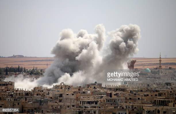 Smoke rises from buildings following a reported air strike on a rebelheld area in the southern Syrian city of Daraa on June 14 2017 / AFP PHOTO /...
