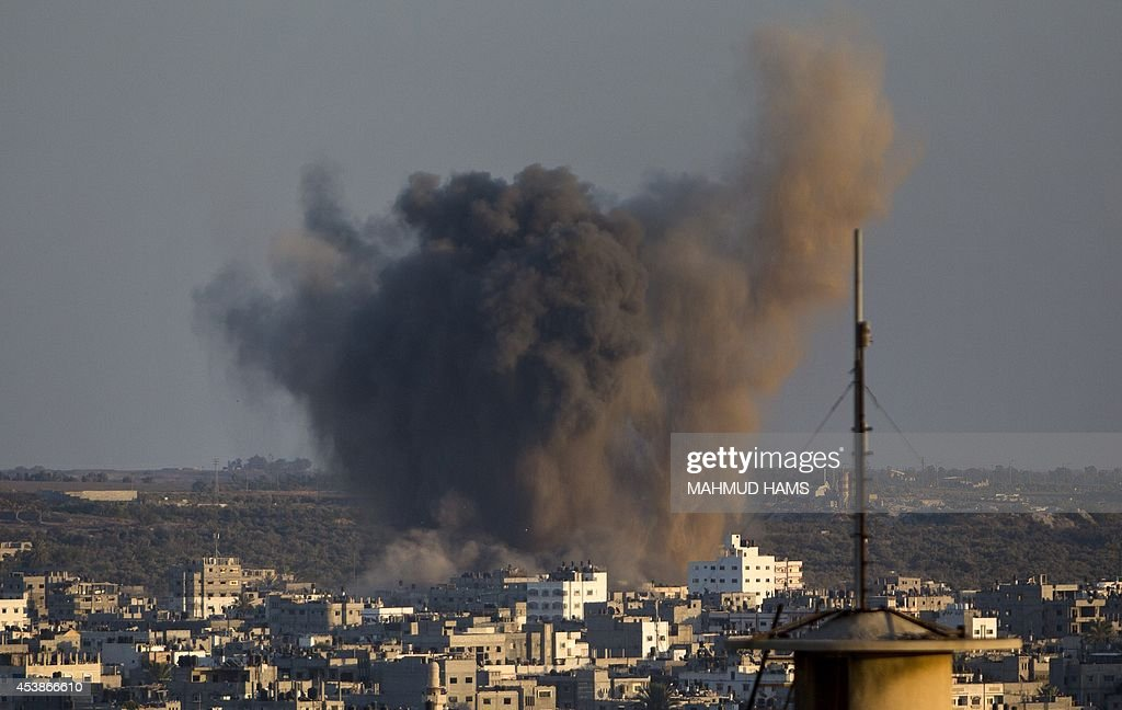 Smoke rises from buildings following an Israeli air strike on Gaza City on August 20, 2014. Israeli warplanes pounded Gaza as furious mourners buried the wife and child of Hamas's top military commander, baying for revenge as nine days of calm exploded into bloodshed.