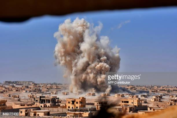 TOPSHOT Smoke rises from buildings in the area of Bughayliyah on the northern outskirts of Deir Ezzor on September 13 as Syrian forces advance during...