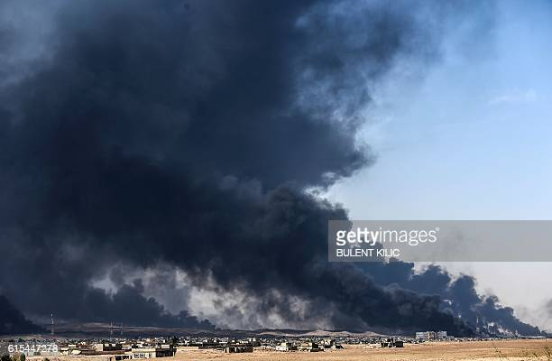TOPSHOT Smoke rises from burning oil wells on October 18 2016 near the town of Qayyarah south of Mosul during the operation to recapture the city...
